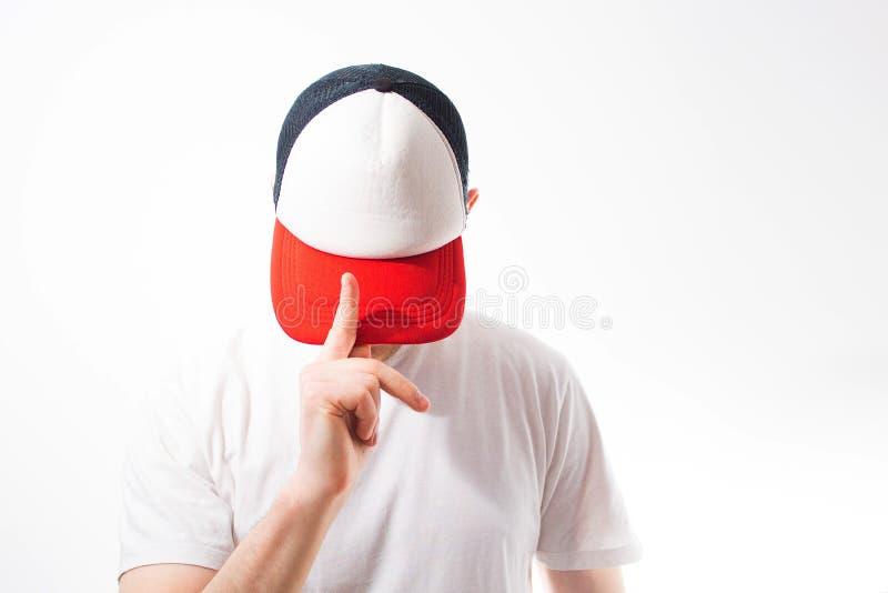 O homem, indivíduo no boné de beisebol branco, vermelho vazio, em um b branco fotos de stock