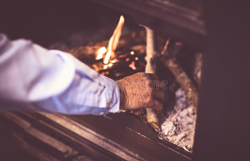 O homem inflama um fogo na chaminé imagem de stock royalty free