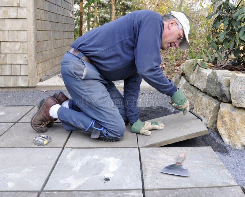 O homem instala o flagstone no pátio foto de stock
