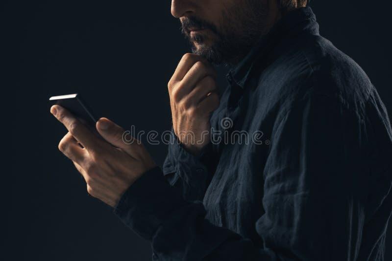 O homem interessado pensativo está lendo a mensagem de texto imagens de stock