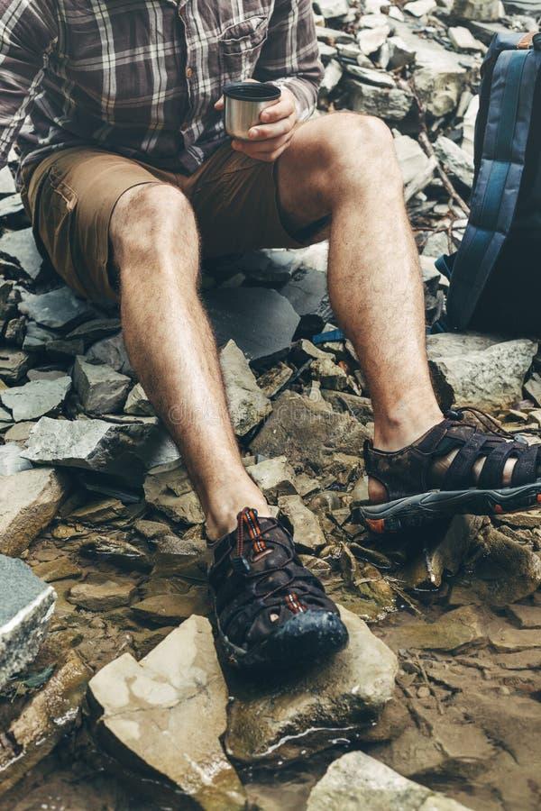 O homem irreconhecível do caminhante derrama o chá ou o café da garrafa térmica no fundo da cachoeira Tema da caminhada e do laze imagens de stock