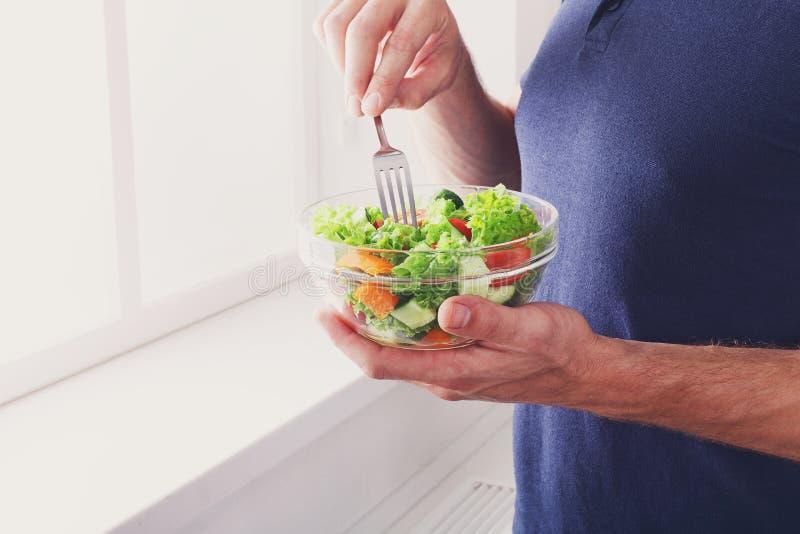 O homem irreconhecível tem o almoço saudável, comendo a salada do vegetal da dieta fotografia de stock