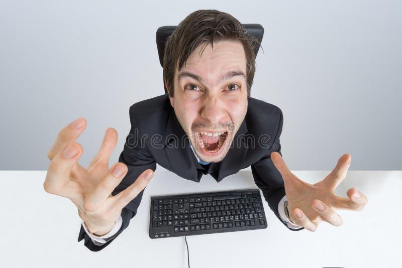 O homem irritado e frustrante está trabalhando com computador e gritaria imagem de stock royalty free