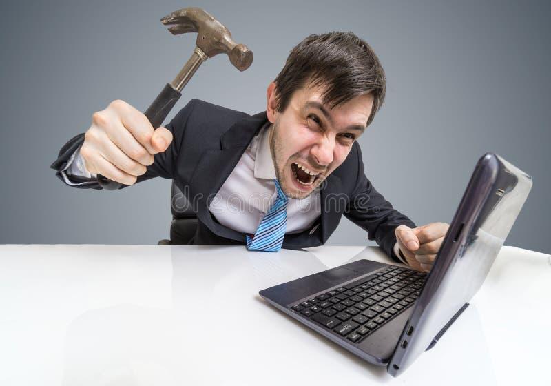 O homem irritado e louco está trabalhando com portátil Está indo danificar o caderno com martelo fotos de stock royalty free