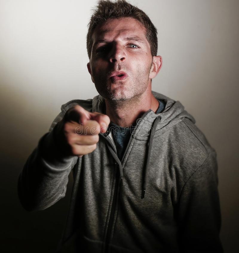 O homem irritado e virado atrativo novo que olha com intenso e que ameaça eyes como se discutindo apontar com o dedo no aggressi foto de stock