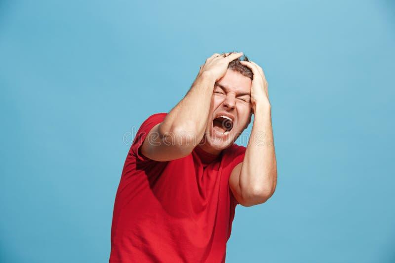 O homem irritado emocional novo que grita no fundo azul do estúdio fotografia de stock royalty free