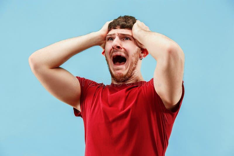 O homem irritado emocional novo que grita no fundo azul do estúdio foto de stock royalty free