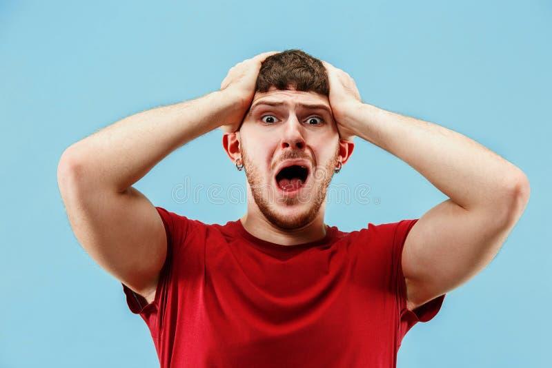 O homem irritado emocional novo que grita no fundo azul do estúdio imagem de stock