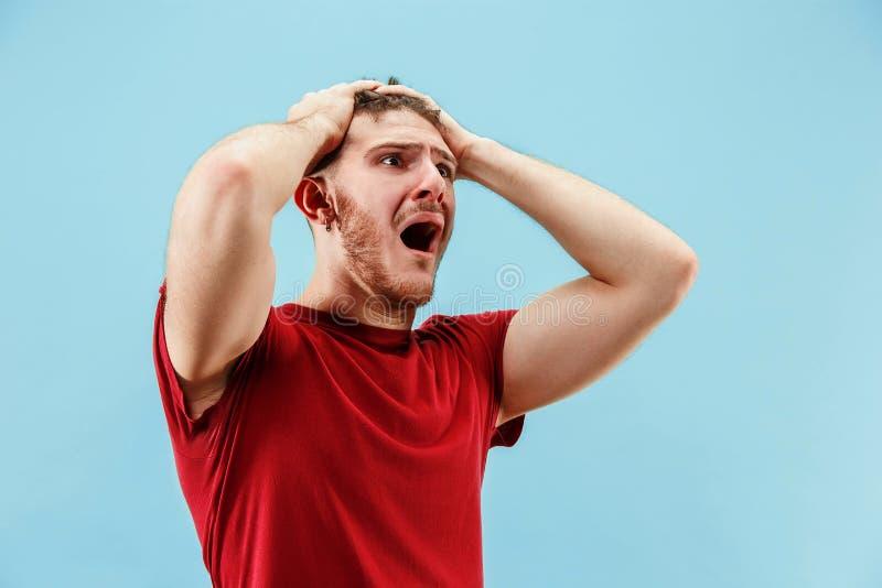O homem irritado emocional novo que grita no fundo azul do estúdio fotos de stock