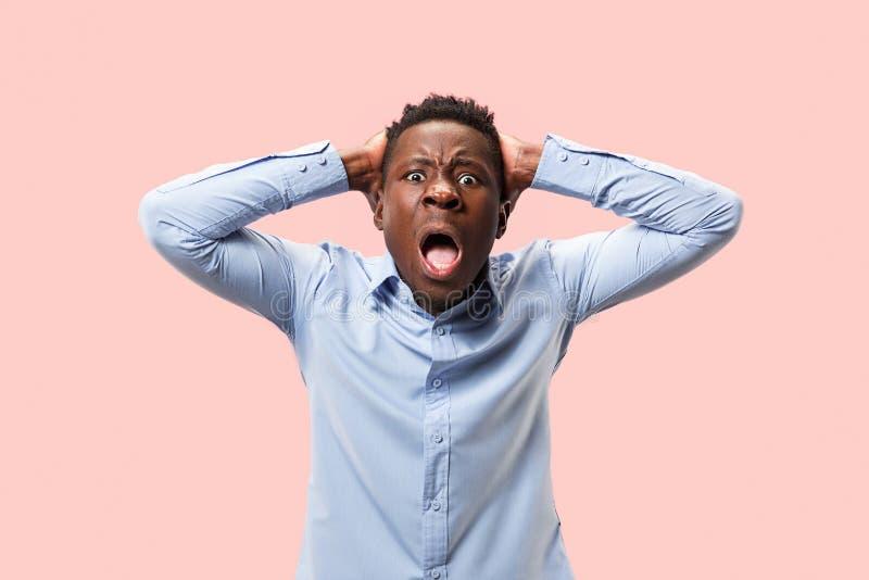 O homem irritado emocional novo que grita no fundo cor-de-rosa do estúdio imagens de stock