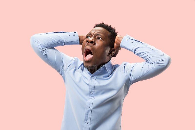 O homem irritado emocional novo que grita no fundo cor-de-rosa do estúdio fotos de stock royalty free