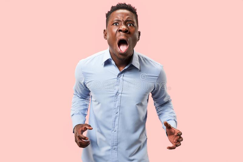 O homem irritado emocional novo que grita no fundo cor-de-rosa do estúdio imagem de stock royalty free