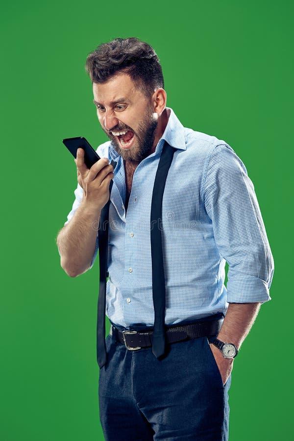 O homem irritado emocional novo que grita no fundo verde do estúdio imagens de stock royalty free