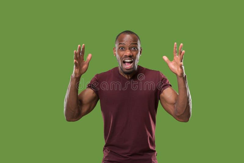 O homem irritado emocional novo que grita no fundo verde do estúdio fotografia de stock