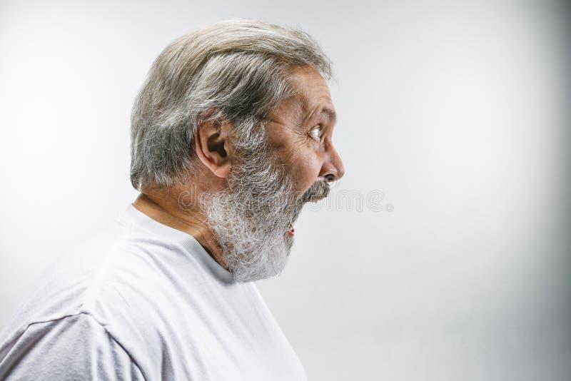 O homem irritado emocional superior que grita no fundo branco do estúdio imagens de stock