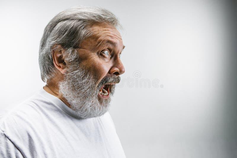 O homem irritado emocional superior que grita no fundo branco do estúdio fotografia de stock