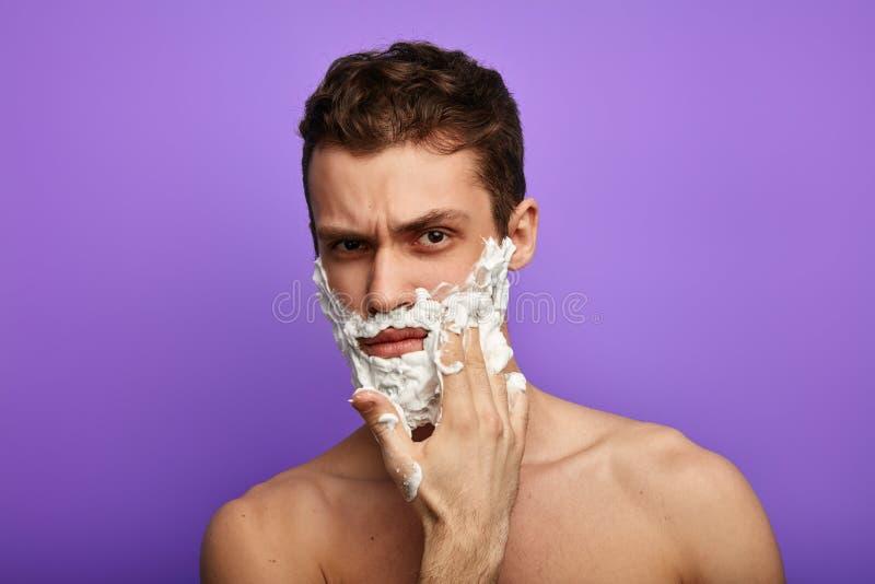 O homem irritado frustrante infeliz não quer barbear sua barba grossa foto de stock royalty free