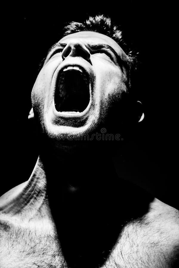 O homem irritado grita em um fundo preto, agressão fotos de stock