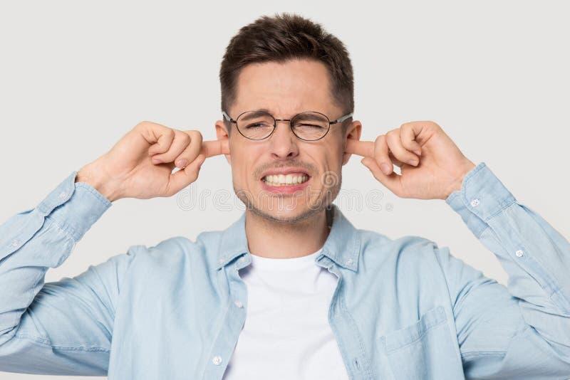 O homem irritado nos vidros cobre as orelhas que evitam o som alto foto de stock