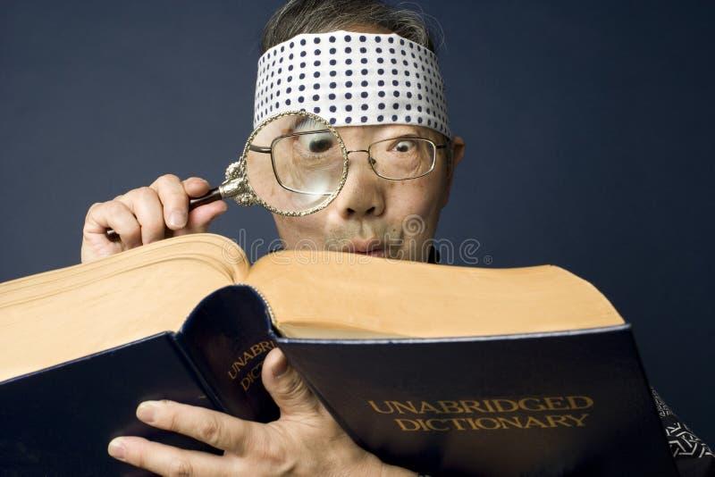 O homem japonês sênior examina o dicionário fotos de stock royalty free