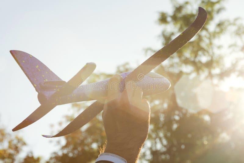 O homem joga com um avião do brinquedo no por do sol e nos sonhos da viagem Mão com fim pequeno do plano acima Avião do brinquedo fotografia de stock