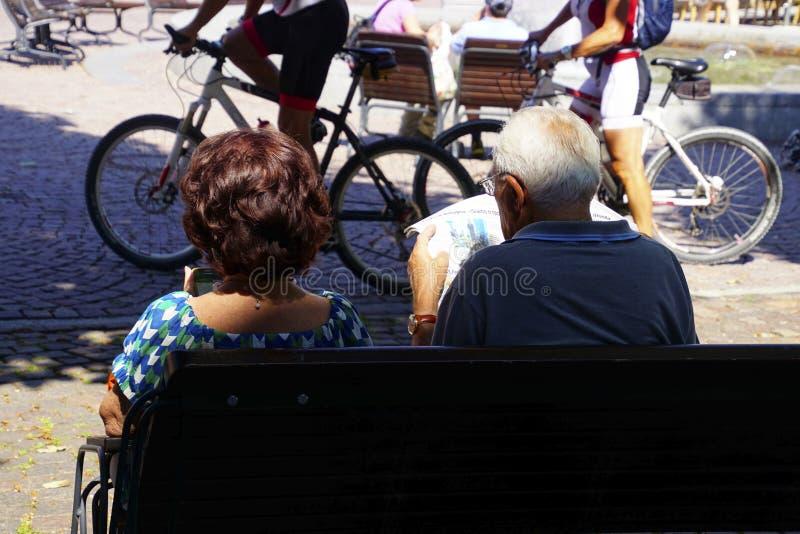 O homem lê o jornal na praça da cidade imagens de stock royalty free