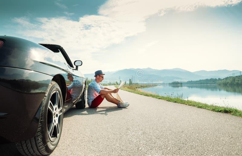 O homem lê o mapa de estradas que senta-se perto de seu cabriolet imagem de stock royalty free