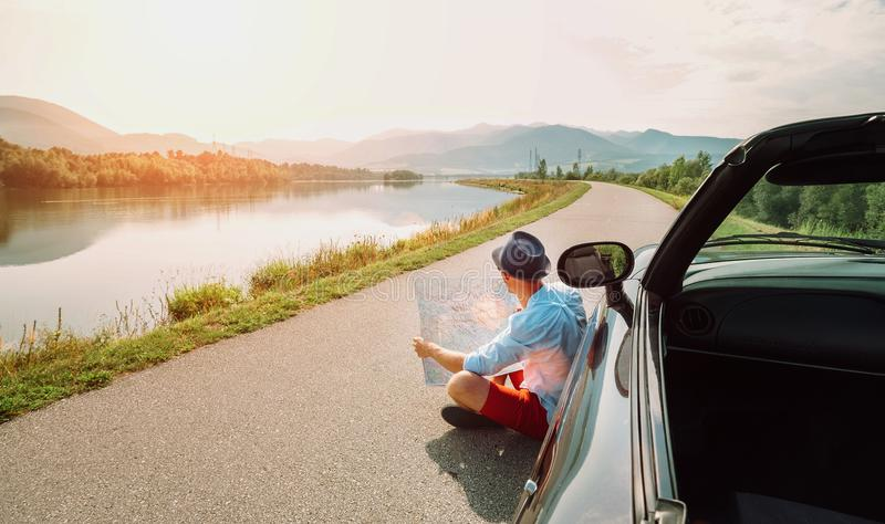 O homem lê o mapa de estradas que senta-se perto de seu cabriolet no mo pitoresco fotografia de stock