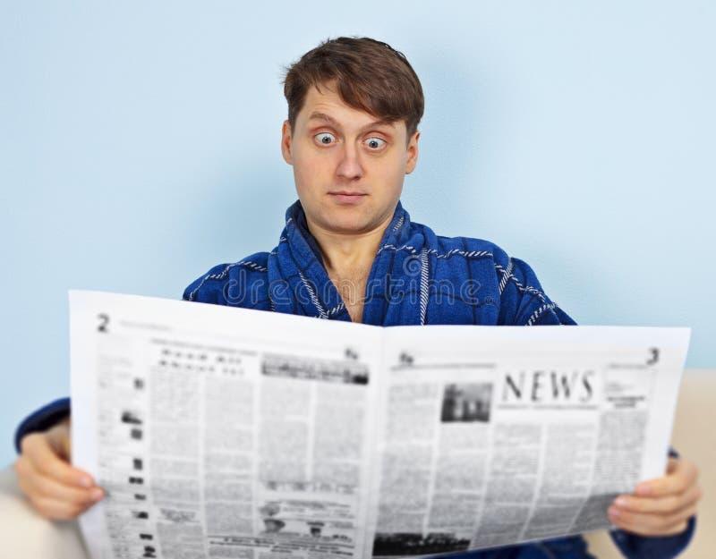 O homem lê um jornal com uma admiração foto de stock royalty free