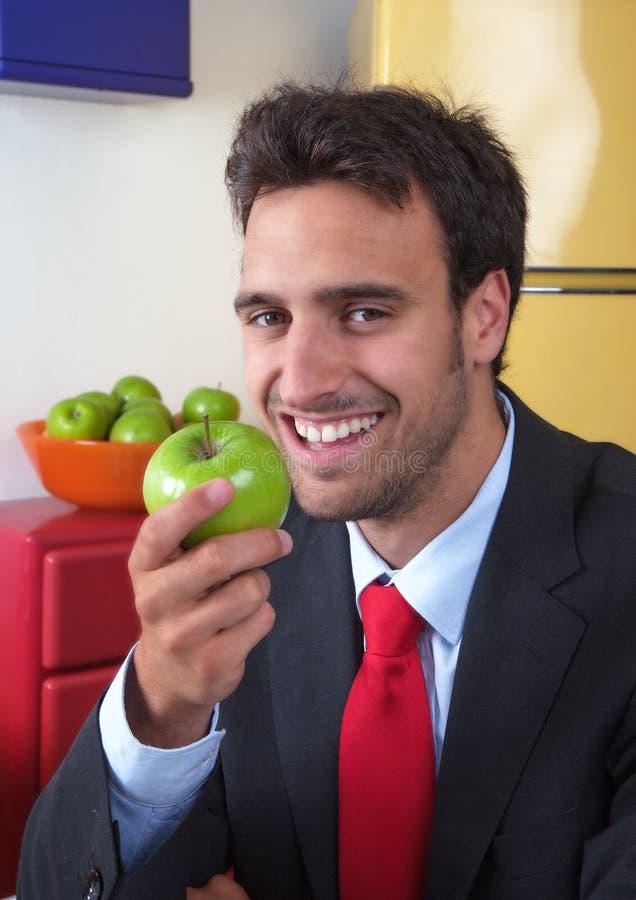 O homem latin de riso come uma maçã fotografia de stock