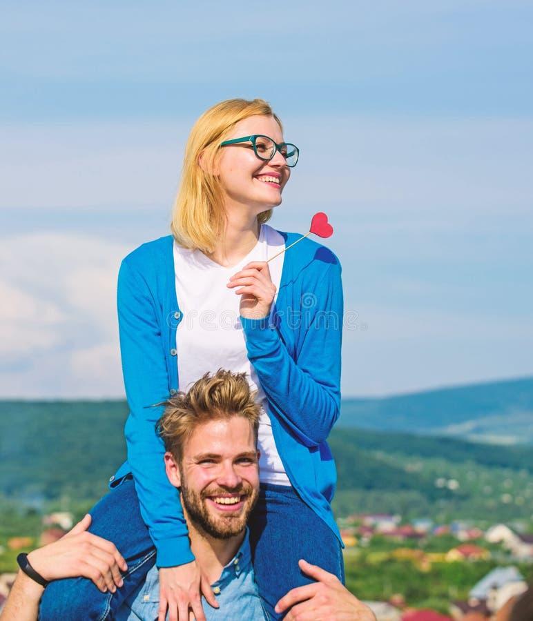 O homem leva a amiga em ombros, fundo do céu Conceito romântico da data A mulher guarda o coração no símbolo da vara do amor imagem de stock
