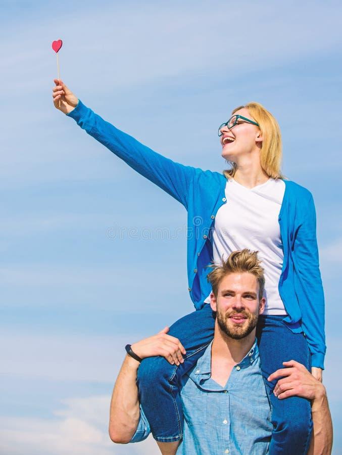 O homem leva a amiga em ombros, fundo do céu Data feliz dos pares que tem o divertimento junto A mulher guarda o coração na vara fotos de stock royalty free