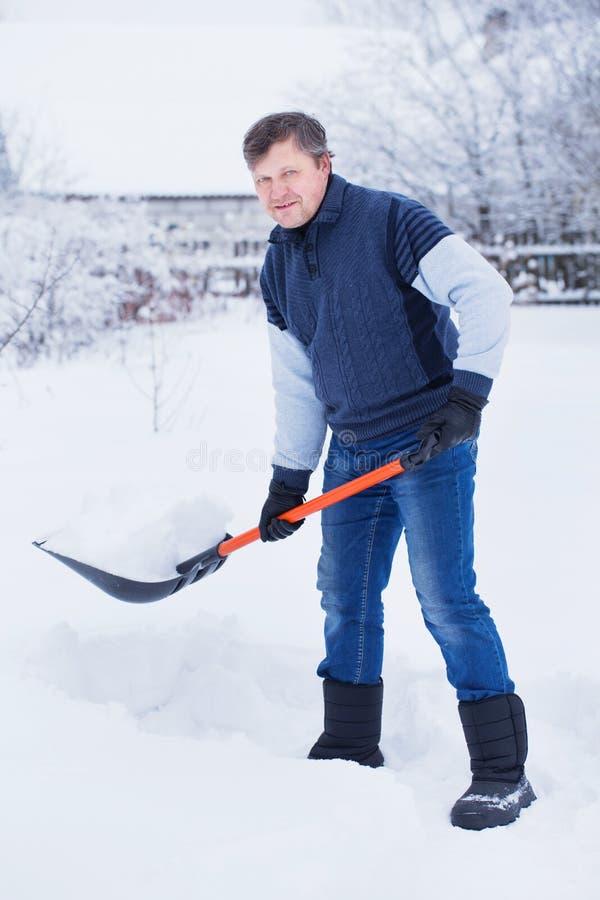 O homem limpa a p? da neve fotografia de stock royalty free