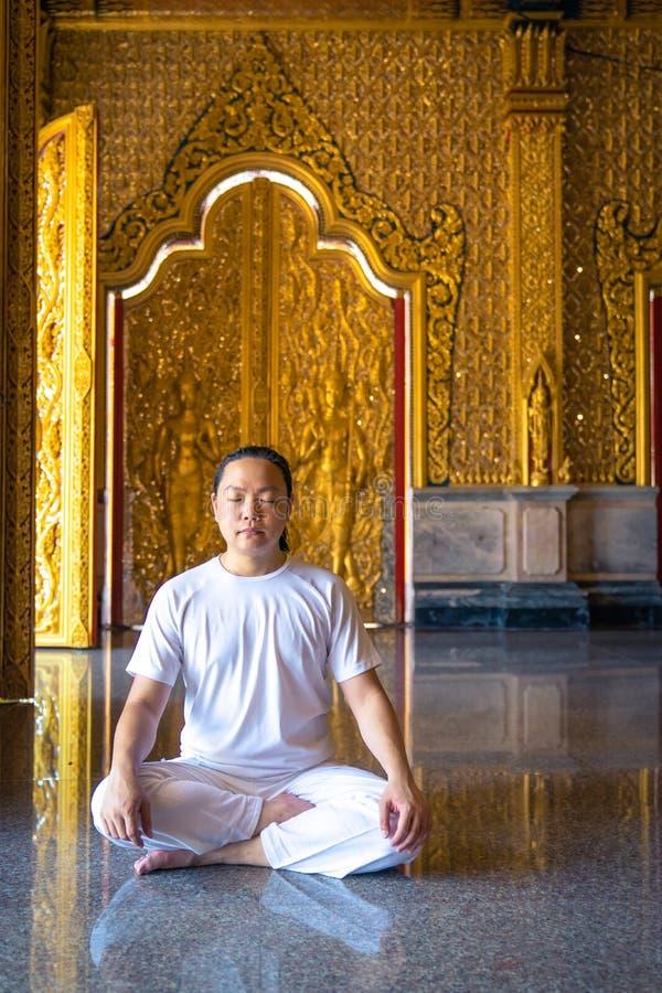 O homem longo asiático do cabelo relaxa a meditação com todo o traje branco para sentar-se na frente do papel de parede no templo imagem de stock