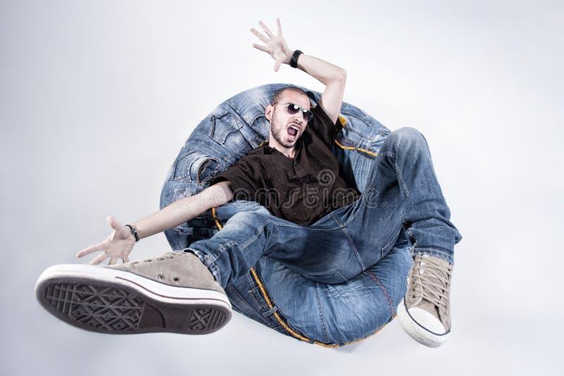 O homem louco engraçado vestiu-se nas calças de brim e nas sapatilhas fotografia de stock royalty free