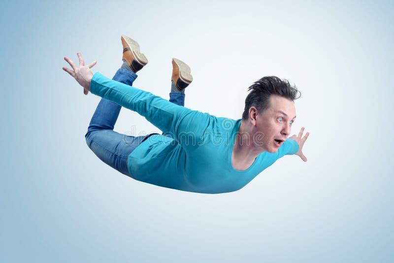O homem louco na camisa e nas calças de brim está voando no céu Conceito da ligação em ponte foto de stock
