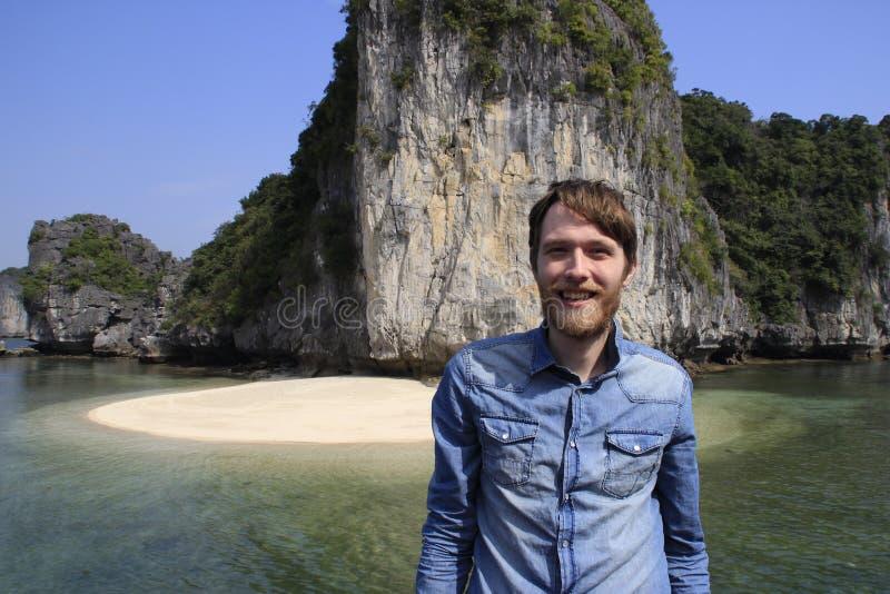 O homem louro atrativo branco novo com uma barba em uma camisa azul da sarja de Nimes está na perspectiva de uma rocha e do mar n foto de stock
