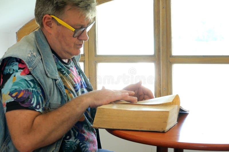 O homem maduro considerável senta-se na tabela e nos rolos através do livro velho, talvez do manual do telefone ou do diretório g fotos de stock