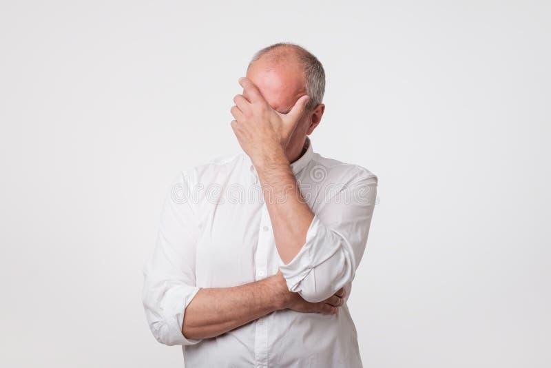 O homem maduro desagradado na camisa branca que cobre sua cara com cede o fundo cinzento imagens de stock