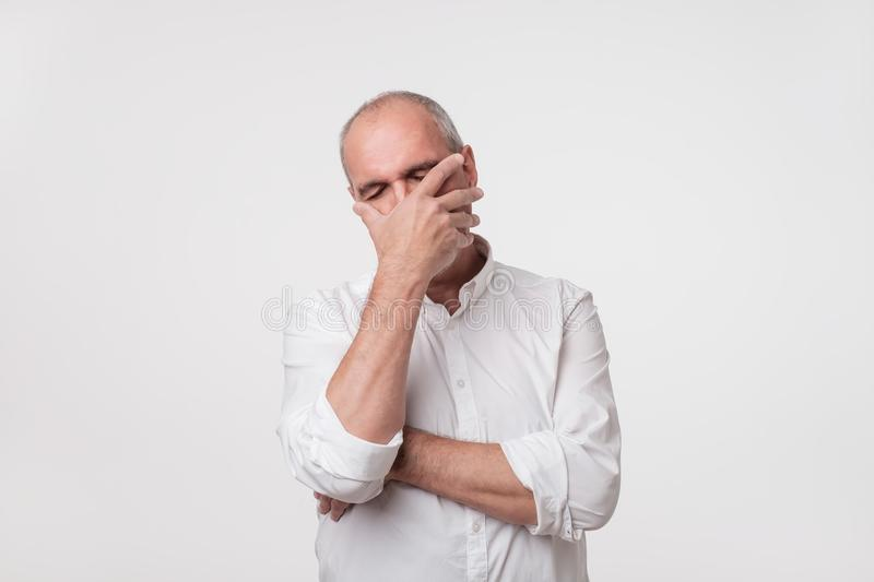 O homem maduro desagradado na camisa branca que cobre sua cara com cede o fundo cinzento imagem de stock royalty free