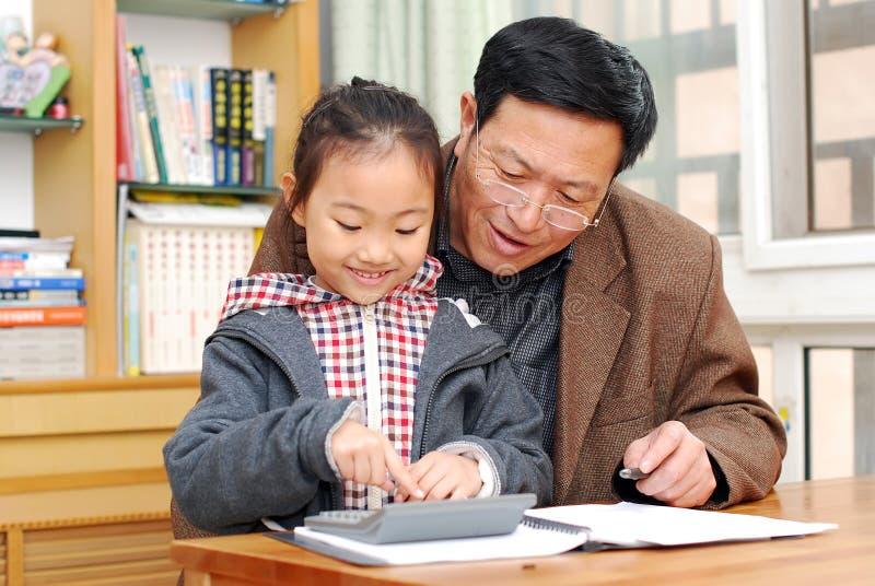 O homem maduro está ensinando o cálculo da menina foto de stock
