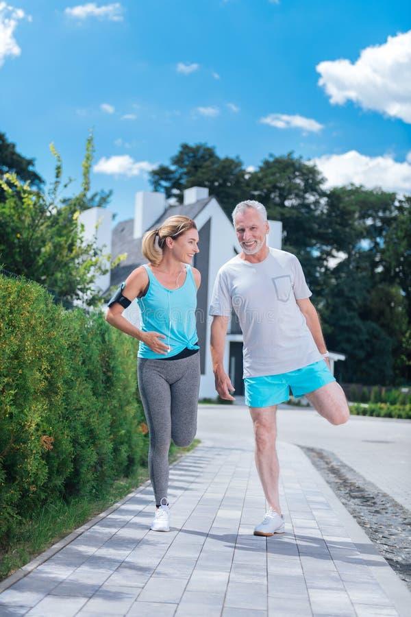 O homem maduro farpado que sente feliz ao fazer a manhã exercita com esposa fotos de stock