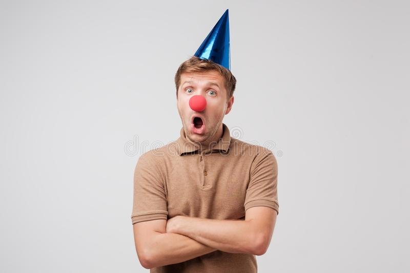 O homem maduro no tampão do aniversário e no nariz vermelho do palhaço é chocado com presente fotos de stock royalty free