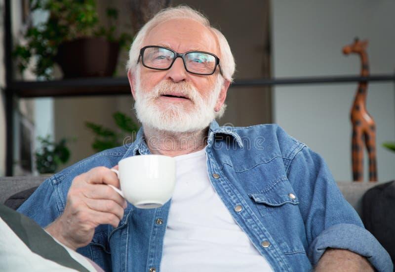O homem maduro pensativo que aprecia anota o café imagens de stock