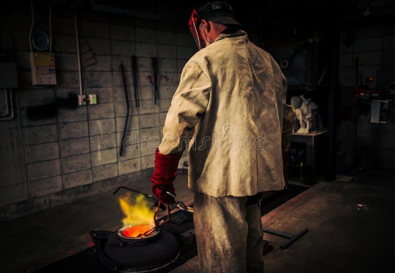O homem maduro verifica o calor do cadinho para ver se há o bronze quente de metal derrama imagem de stock