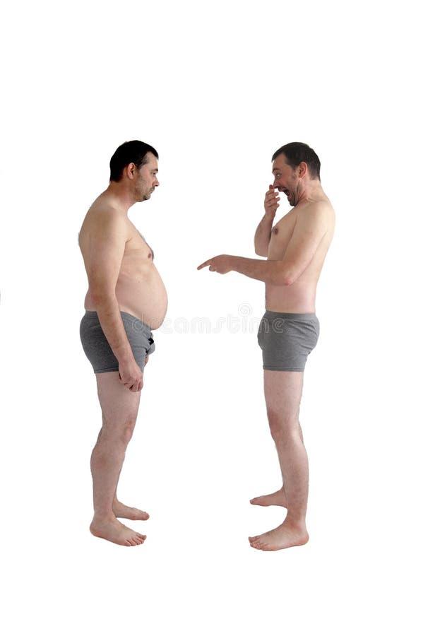 O homem magro ri de seu auto gordo fotos de stock