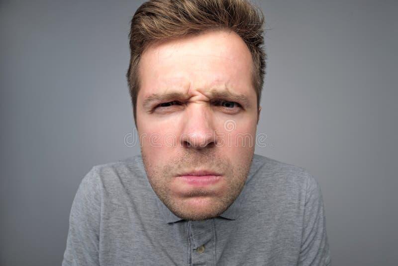 O homem mantém os bordos pressionados frustrou a cara olhada de sobrancelhas franzidas fotografia de stock