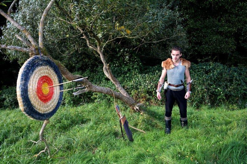 O homem medieval está na natureza A seta, curva e treme suportes além de e alvo da palha com setas fotografia de stock