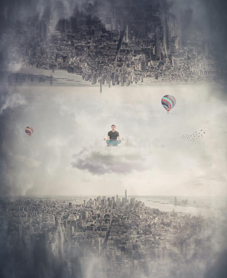 O homem medita assentado em uma nuvem de flutuação entre dois mundos paralelos imaginários imagens de stock royalty free