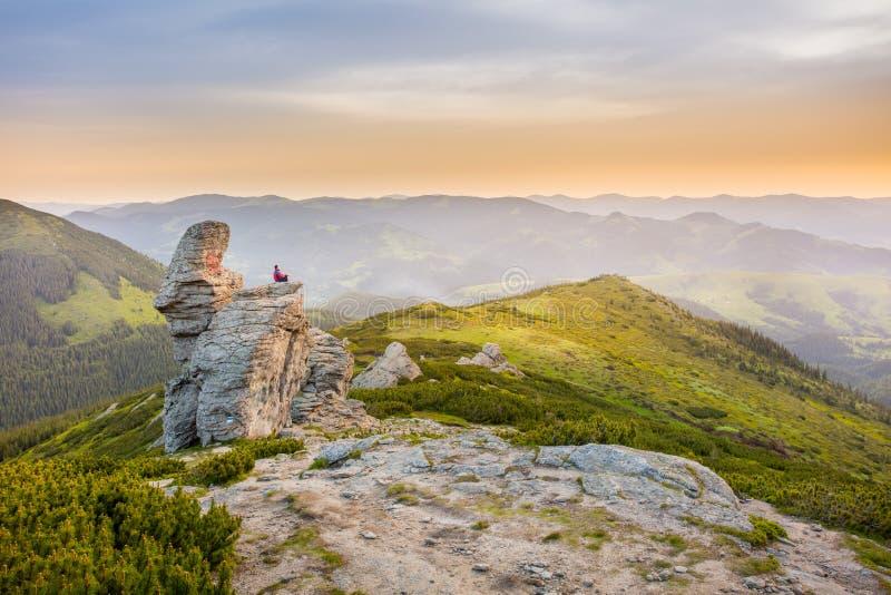 O homem medita sobre uma rocha nas montanhas imagens de stock royalty free